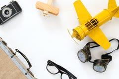Vintage toy plane, old photo camera, pilot glasses. Top view of vintage yellow toy plane, old photo camera, pilot glasses and suitcase Royalty Free Stock Photography