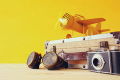 vintage toy plane and old suitcase next to pilot glasses Stock Photos