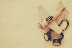 Vintage toy plane and pilot glasses. Sepia style image. Top view of vintage toy plane and pilot glasses. Sepia style image stock images