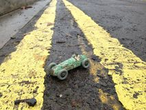 Vintage toy racing car & driver, with worn green paint original patina, between double yellow line on a road. Stock Photo