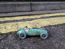 Vintage toy racing car & driver with worn green patina, in front of double yellow line no parking restriction. Royalty Free Stock Images