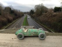 Vintage toy racing car, green worn paint close up, seen from above a main road blurred background Stock Image