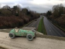 Vintage toy racing car, green worn paint close up, seen from above a main road blurred background Stock Photo