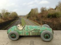 Vintage toy racing car, green worn paint close up, seen from above a main road blurred background Stock Photos