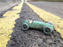 Vintage toy racing car, taken on a real road background showing double yellow lines going into the distance, diagonal perspective Stock Image