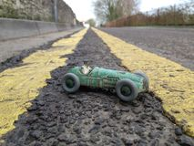 Vintage toy racing car, taken on a real road background showing double yellow lines going into the distance, diagonal perspective Royalty Free Stock Photo