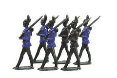Vintage Toy Soldiers Marching. A set of six vintage metal toy soldiers marching in formation against a white background Royalty Free Stock Photo