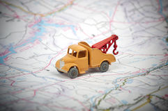Vintage toy tow truck. On a road map Royalty Free Stock Photo
