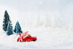 Vintage Toy Truck and Candy canes. 1950`s antique vintage red truck hauling a candy canes home through a snowy winter wonder land with pine trees in background Royalty Free Stock Images