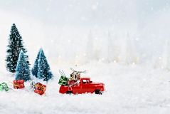 Vintage Toy Truck and Christmas Gifts. 1950`s antique vintage red truck hauling a Christmas gifts home through a snowy winter wonder land with pine trees Stock Images