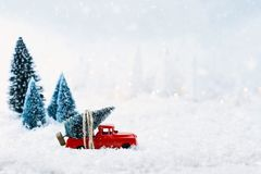 Vintage Toy Truck and Christmas Tree. 1950`s antique vintage red truck hauling a Christmas tree home through a snowy winter wonder land. Extreme shallow depth of Stock Photo