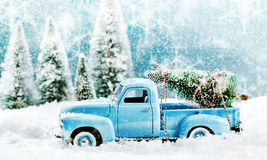 Vintage toy truck fetching a Christmas tree. From a pine forest in a winter snow storm driving through thick snow with a tree loaded on the back, side view stock photos