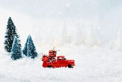 Vintage Toy Truck Loaded with Christmas Gifts. 1950`s antique vintage red truck hauling a Christmas gifts home through a snowy winter wonder land with pine trees Royalty Free Stock Photos