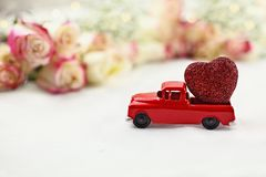 Vintage Toy Truck and Valentine`s Day Heart. 1950`s antique vintage red truck hauling a glittery red heart past a roll of beautiful long stem roses. Extreme Royalty Free Stock Photography