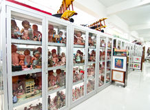 Vintage toys. Collection of vintage toys in a row of glass display cabinets showing dolls from many parts of the world and on top of the cabinets biplanes with stock photography