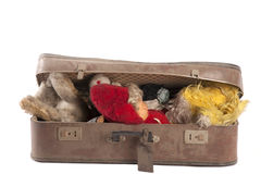 Vintage toys. Stuffed in a big, dusty old suitcase royalty free stock photography