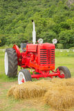 Vintage Tractor. An old red retro tractor in a field stock photo