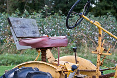 Vintage Tractor by Cottonfield. Closeup of an antique tractor sitting next to a cotton field Stock Photography