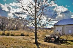 Vintage tractor and implement in front of barn Stock Photo