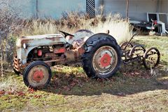 Vintage tractor and implement in front of barn Stock Images