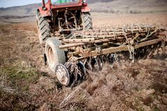 Vintage tractor plowing the field Stock Images