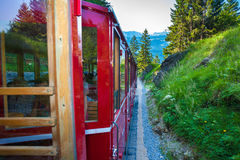 Vintage train eith red carriages cogwheel railway going to Schaf Stock Photography
