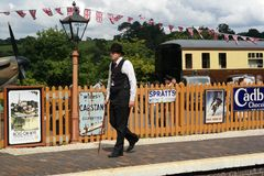 Vintage train platform. Man in vintage travel recreation. Platform of old steam train line recreation with posters,bunting and train carriage in bright sun Royalty Free Stock Images