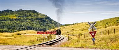 Vintage Train at a Railroad Crossing. Chama NM, USA, Sept. 19, 2017: A vintage steam locomoitve from the Cumbres & Toltec railroad approaches a railroad crossing Royalty Free Stock Image