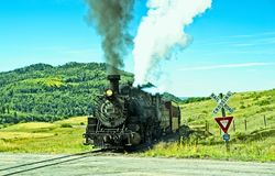 Vintage Train at a Railroad Crossing. Chama NM, USA, Sept. 19, 2017: A vintage steam locomoitve from the Cumbres & Toltec railroad approaches a railroad crossing Royalty Free Stock Photography