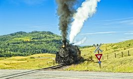 Vintage Train at a Railroad Crossing. Chama NM, USA, Sept. 19, 2017: A vintage steam locomoitve from the Cumbres & Toltec railroad approaches a railroad crossing Stock Photos