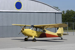 Vintage Trainer Aircraft Parked By Airport Hanger stock photography