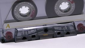 Vintage Transparent Audio Cassette Rotates on White Background. Retro tape cassette with a blank label. Old music. Close-up stock footage