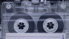 Playing cassette background. Vintage transparent cassette playing inside deck stock footage