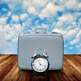 Vintage travel bag with alarm clock on wooden deck. Time to travel concept Royalty Free Stock Photo