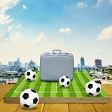 Vintage travel bag on football game board Royalty Free Stock Photos