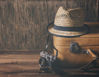 Vintage travel concept. Vintage case, hipster hat,  and retro camera on wooden background still life.. Summer holiday vacation and adventure traveling concept Stock Photo