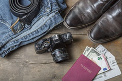 Vintage travel luggage. Jeans, Belt, leather boots, vintage camera and passport with tickets and money on a rustic wooden background Royalty Free Stock Photos