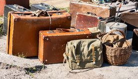 Vintage travel luggage with old suitcases and basket. In sunny day Stock Photo