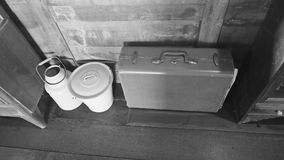 Vintage travel luggage on wooden floor with retro tin buckets. Vintage travel luggage on wooden floor with retro tin buckets in black and white background Stock Photography