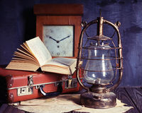 Vintage travel still life. With kerosene lamp, book and suitcase Royalty Free Stock Photography