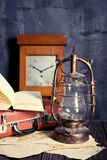 Vintage travel still life. With kerosene lamp, book and suitcase Stock Photo