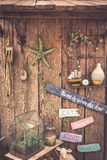 Vintage travel still life on old wooden fence with rope, starfish, compass, wooden signs and accessories Stock Image