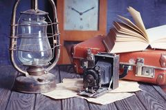 Vintage travel still life. With kerosene lamp, book, old camera and suitcase Stock Images