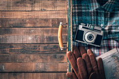Vintage traveler packing. Hipster traveler's old suitcase with vintage camera, map and gloves, blank copy space on the left Royalty Free Stock Photo