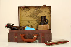Vintage Traveler's Kit. A Opened Suit Case with empty Drinks and a Harmonica Stock Images