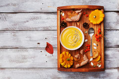 Vintage tray with autumn pumpkin soup decorated sesame seeds and thyme leaf in white bowl on rustic wooden table top view. Stock Photo