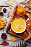 Vintage tray with warm autumn pumpkin soup decorated seeds and thyme in white bowl on rustic wooden table top view. Llifestyle shot for halloween menu Royalty Free Stock Photo
