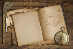 Vintage treasure map in open book with compass and old ruler Royalty Free Stock Image