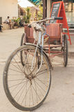 Vintage Tricycle. An old tricycle parking in front of a coffee shop Stock Photo