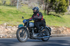 Vintage Triumph motorcycle on country road. Adelaide, Australia - September 25, 2016: Vintage Triumph motorcycle on country roads near the town of Birdwood Stock Images